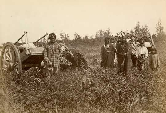 Black and white photograph of Ojibwe with Red River carts near Fort Dufferin, Manitoba, Canada,