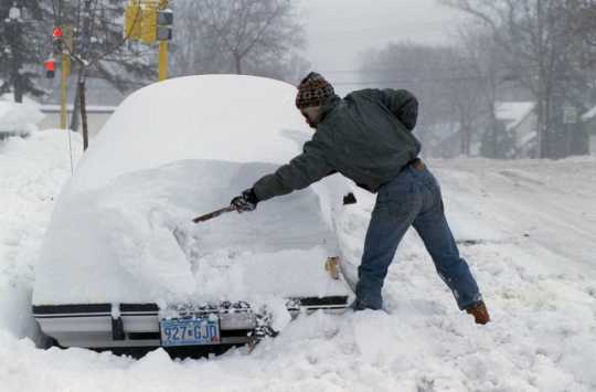 Color image of a resident of Minneapolis digging a car out of the snow after the Halloween Blizzard, 1991. Photograph by Rita Reed, Minneapolis Star Tribune.