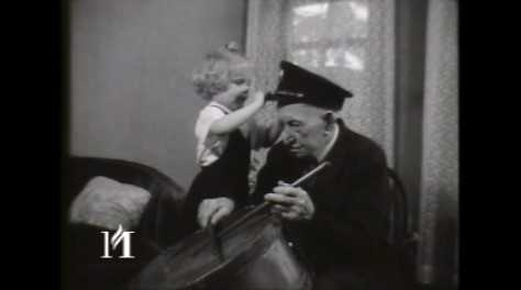 "Film titled ""Albert Woolson Before Death."" It shows Albert Woolson holding his Civil War portrait, playing a drum, smoking a cigar, and receiving bags of mail. Black and white, 16mm, sound film, August 2, 1956. KSTP-TV Archive, Minnesota Historical Society, St. Paul. To view the clip, click the link below."