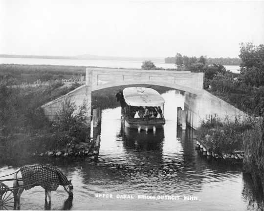 photograph of small steamboat passing under a bridge