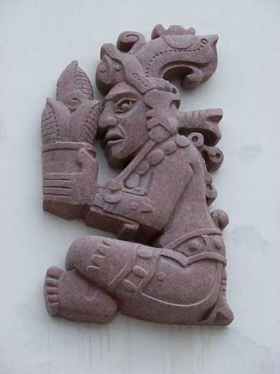 Color image of a corn god holding an ear of corn. Photograph by Wikimedia Commons user ŠJů, 2012.
