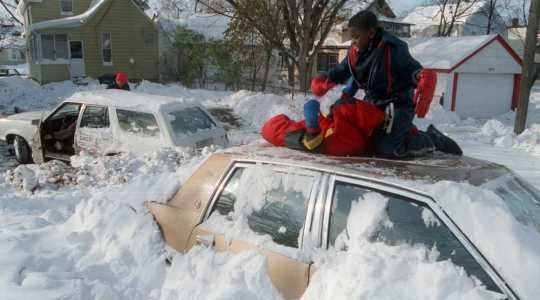 Color image of children playing on top of a car after the Halloween Blizzard, 1991. Photograph by Marlin Levison, Minneapolis Star Tribune.