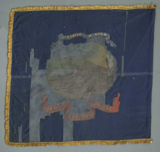 The Fourth Minnesota battle flag is blue with gold fringe. It is missing a large portion of the center, but a motto and image are still somewhat visible. This is the reverse side.