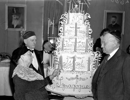 Black and white photograph of congregants lighting candles on a cake at the fiftieth anniversary celebration for Kenesseth Israel Synagogue in Minneapolis, c.1935.