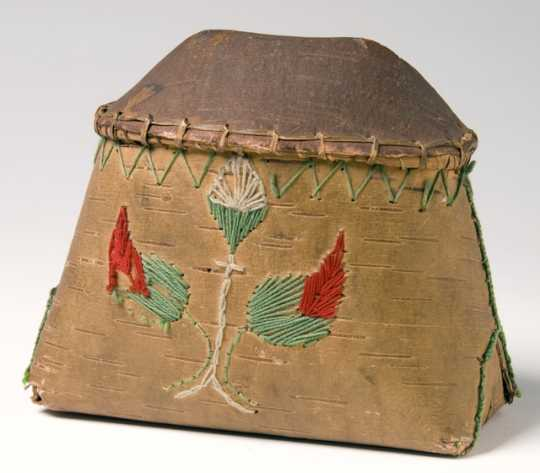 Miniature birchbark makak (Ojibwe storage basket) decorated in floral motifs employing colored cord and yarn. The makak is filled with maple sugar.