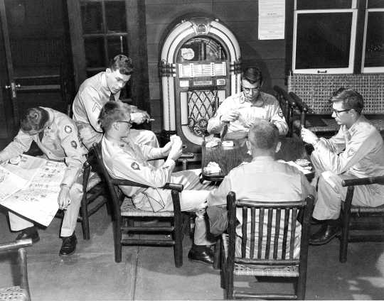 Black and white photograph of after-hours relaxation in Camp Ripley's Enlisted Service Club, 1958.