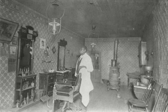 Black and white photograph of African American barber Prince Honeycutt in his Fergus Falls shop, c.1900.