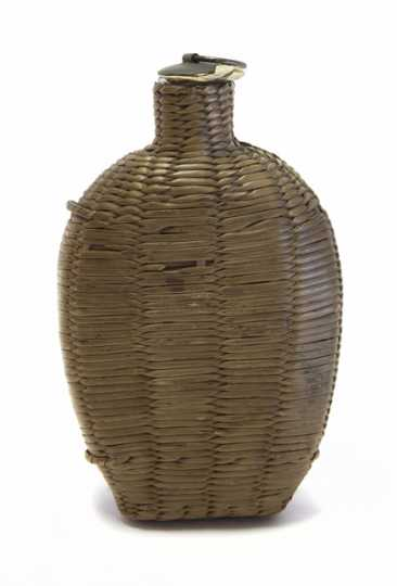 Wicker covered glass canteen.