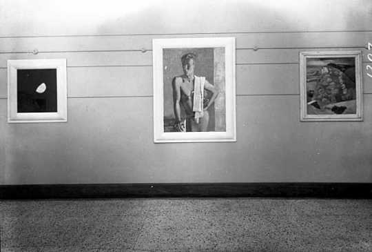 Black and white photograph of paintings by Clement Haupers on exhibit, c.1940.