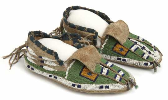 Pair of sinew-sewn leather moccasins with a rawhide sole. Made by Dakota Indians in the late nineteenth or early twentieth century.