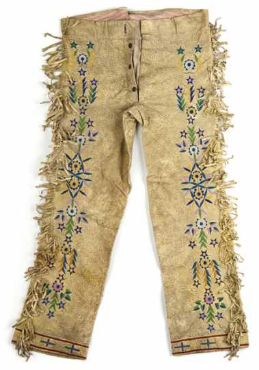 Color image of a pair of Lakota hide trousers with extensive bead and quillwork decoration. Made with a combination of machine and hand sewing. Collected at the Cheyenne River Indian Reservation, c.1900.