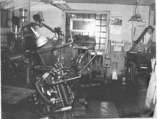 Black and white photograph of a printing machine in the office of the Waconia Patriot. Date and photographer unknown.