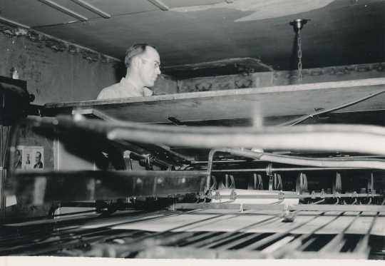 Black and white photograph of a Waconia Patriot employee uses a printing press. Date and photographer unknown.