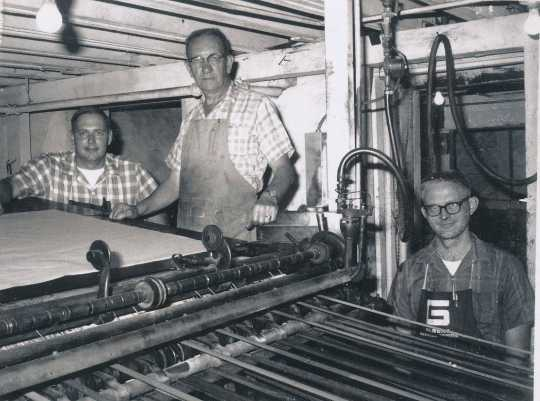 Black and white photograph of staff of the Waconia Patriot at a printing press. Art Wessele is shown in the middle. Date and photographer unknown.