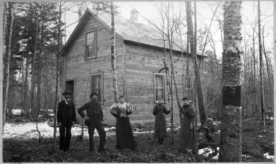 People posed in front of a house built for Hinckley fire victims, after September 1, 1894.