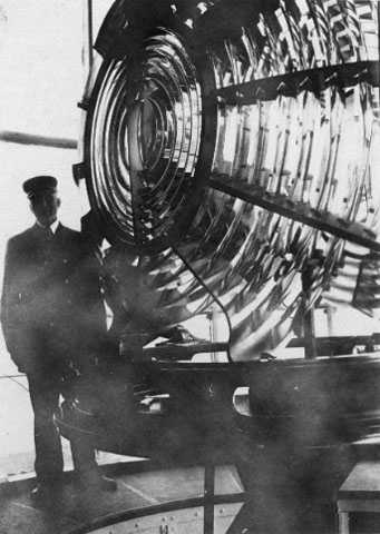 Black and white photograph of Franklin J. Covell by the Split Rock Lighthouse lens.