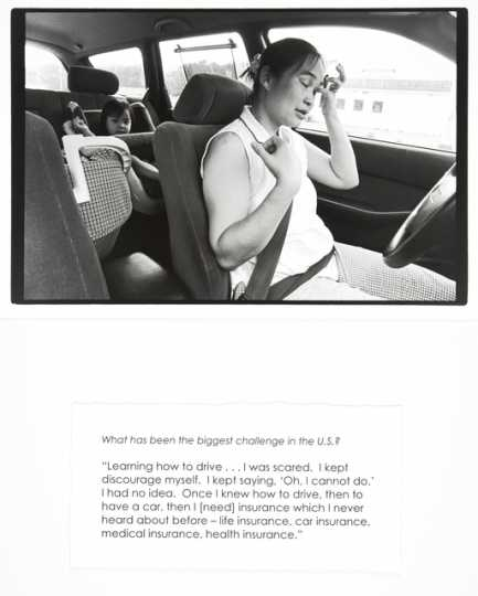 """Black and white photograph of a woman driving a car with a child in the backseat, with accompanying quote, by Jane Kramer, 2004. From collection, """"Photographs and Stories of Refugee Women: Perseverance, Dignity, Strength, Hope, and Peace."""""""