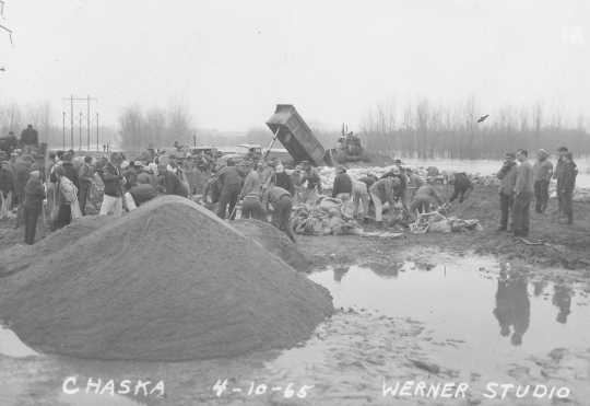 Black and white photograph of the rebuilding dikes in Chaska during flood of 1965. Photographed by Werner Studio, April 10, 1965.