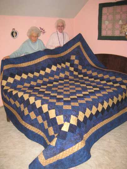 Color image of Anna and Lena Ewert posing with a quilt they made and donated to the Tabor College Carson Center quilt auction, 2009.
