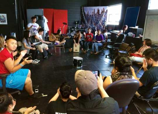 Color image of Hmong youth participate in Art Saves Us: Beyond the Noise, collaboratively creating original music in the Center for Hmong Arts & Culture's (CHAT's) St. Paul studio, May, 2013.