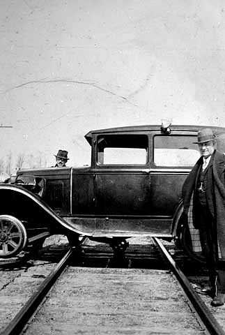 Photograph of a car straddling a railroad track. The car was used to transport Reverend John Sornberger to lumber camps c.1930.