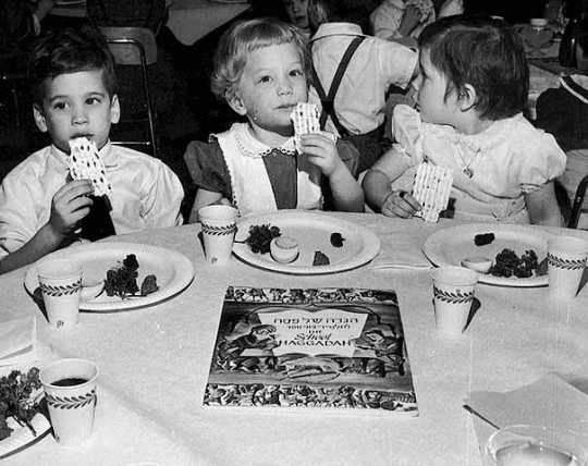 Black and white photograph of three children attending a Passover seder at the St. Paul Talmud Torah, 1960. The children are Susan Hoffman, Lisa Savitt, and Scott Zuckman.