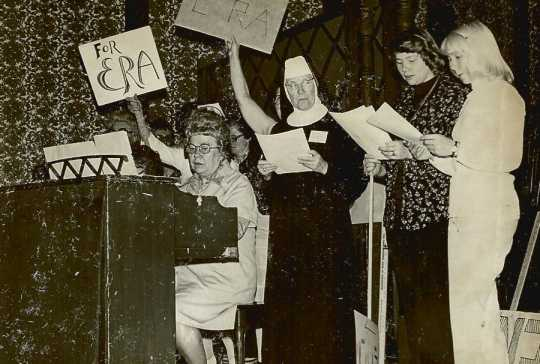 Black and white photograph of Sister Mary Magadalene, Marie Nelson (playing the piano), and other BPWC members sing a song promoting the Equal Rights Amendment, May 1977.