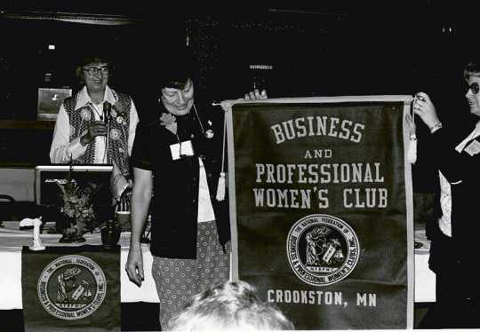 Black and white photograph of Crookston BPW president Betty Brecto watches as BPWC members Eleanor Johnson and Norma Van Horn, two BPW members, reveal the new Crookston BPWC banner on March 11, 1977.