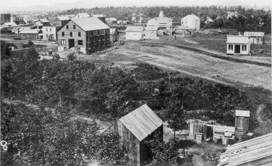 Black and white photograph taken from the St. James Hotel in 1857. The Hennepin Avenue Bridge appears in the background.