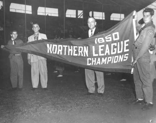 Boy Scouts and Rox management hold up their 1950 championship banner, c.1951. From the Myron Hall Collection, Stearns History Museum and Research Center, St. Cloud.