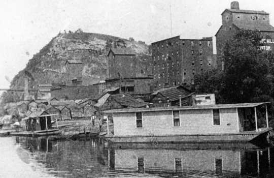 Black and white photograph of Red Wing's crowded riverfront with Barn Bluff in the background, c. 1910