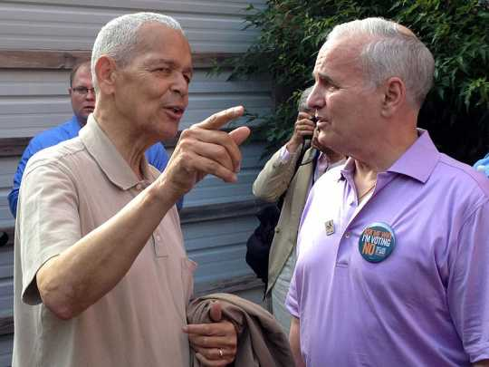 Color image of civil rights leader Julian Bond and Minnesota Governor Mark Dayton confering at a rally held to demonstrate opposition to Minnesota Marriage Amendment 1. Photographed by Bobak Ha'Eri on June 19, 2012.