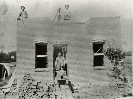 Black and white photograph of a brick house under construction in Meire Grove c.1890.
