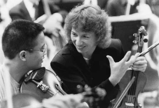 Black and white photograph of SPCO musician Carolyn Daws working with local music students, 1983.