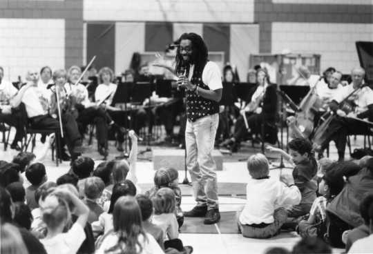 Black and white photograph of Bobby McFerrin & SPCO at Groveland Park Elementary School in St. Paul, 1995.