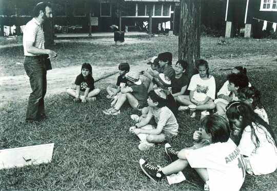Black and white photograph of campers gathering outdoors at Camp Ramah, 1986.