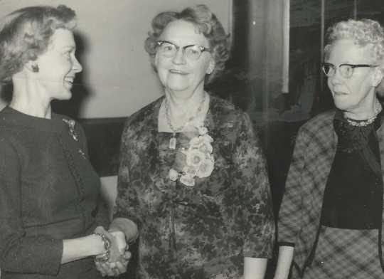 Black and white photograph of Mary Vattendahl, left, presents the 1966 Woman of Achievement award to Clara Berg (center) as Bergetta Logen, a long-time Crookston resident and the BPWC's fourth president (right) looks on, 1966.