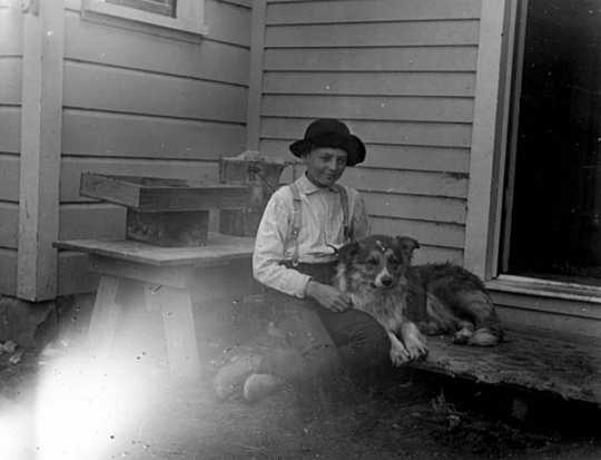 Black and white photograph of Lewis H. Merrill and his dog Mack at the backdoor of the Harrington-Merrill House, 1900.