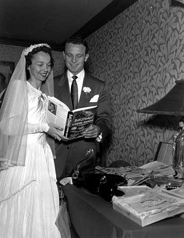Black and white photograph of a wedding in the family of Mr. and Mrs. Frank Uram; bride and groom at gift table looking at Betty Crocker cook book, 1950.