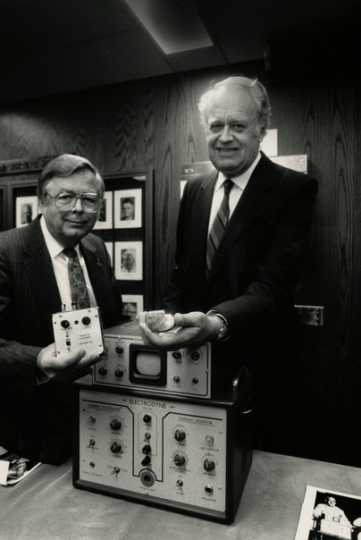 Black and white photograph of Medtronic Founder Earl Bakken and Medtronic CEO Winston Wallin with an early pacemaker model, 1986. Photographed by Jeffrey Grosscup.
