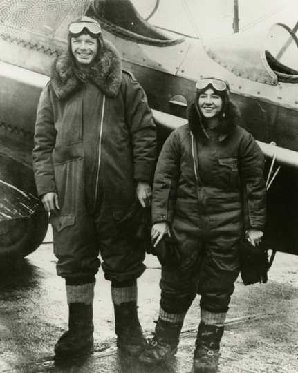 Black and white photograph of Charles and Anne Lindbergh in flight suits next to Lockheed Sirius during their flight across the Northern Pacific, c.1931.