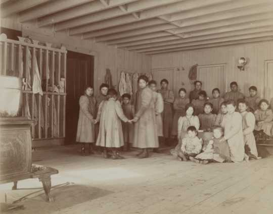 Black and white photograph of students at a Native American board school, c.1900.