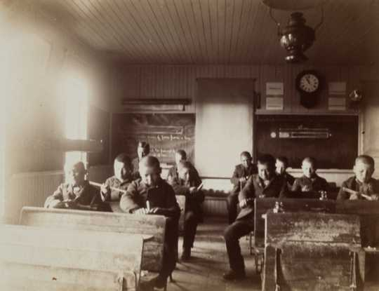 Black and white photograph of students inside a classroom at an Indian boarding school, c.1900.