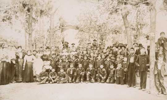 Black and white photograph of students and staff of a Native American boarding school, c.1900.