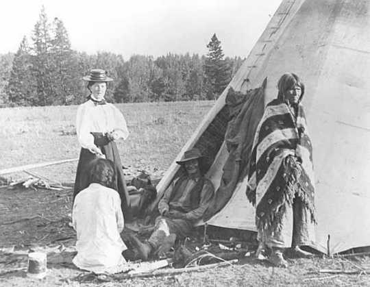 Black and white photograph of Frances Densmore outside of tipi with American Indians, 1900.
