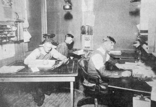 Black and white photograph of the depot agent, engineer, and telegraph operator working inside the Westbrook Depot, 1916.