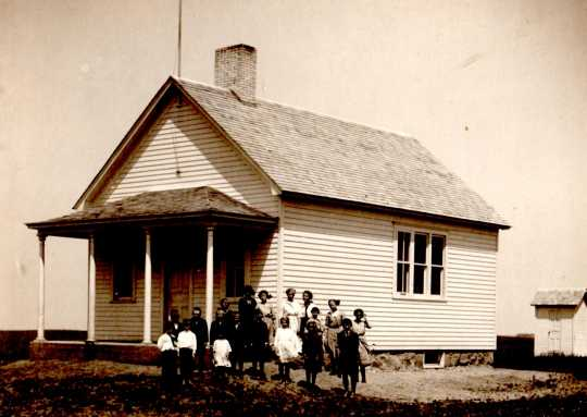 Black and white photograph of students in front of District 112 school in Mason Township, Murray County, 1913.