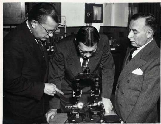 Photograph of Dr. John B. Dalton demonstrating a comparison microscope