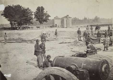 Black and white photograph of men of the First Minnesota Volunteer Infantry in field works after the battlefield of Fair Oaks, Virginia, 1862. Evidence of the newly-attached Company L, the Second Company Minnesota of Sharpshooters, can be seen in the center-right of the photograph: a Sharps breech-loading rifle is hanging over a blanket.