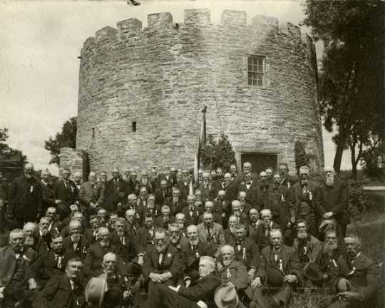 Black and white photograph of a reunion of First Minnesota Volunteer Infantry Regiment, posed in front of Round Tower, 1902.